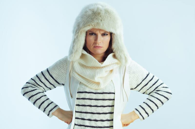 Angry trendy woman on winter light blue background. Portrait of angry trendy woman in white striped sweater, scarf and ear flaps hat on winter light blue royalty free stock photography