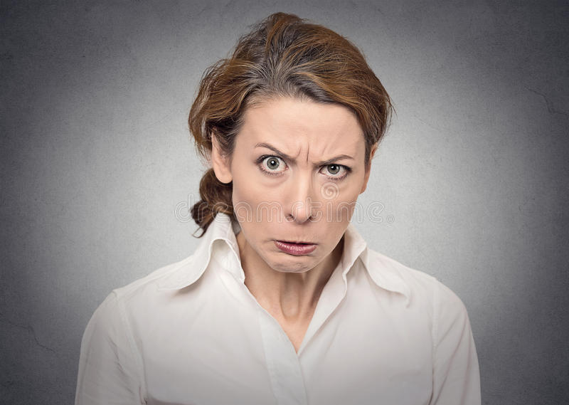 Portrait angry woman. Portrait angry off grumpy woman on grey wall background stock images
