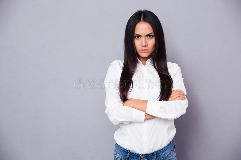Portrait of angry woman standing with arms folded. On gray background stock photo