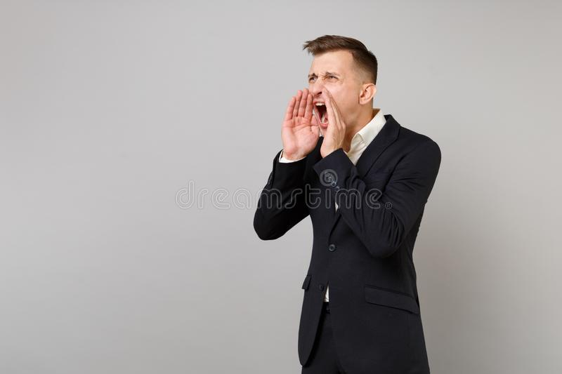 Portrait of angry young business man in classic black suit shirt screaming with hand gesture isolated on grey wall stock photos