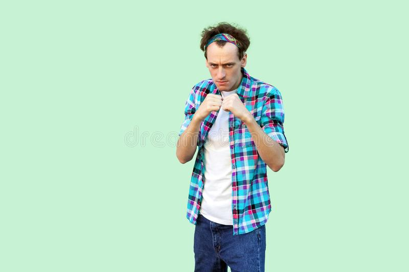 Portrait of angry young man in casual blue checkered shirt and headband standing and looking at camera with boxing fists and ready. To attack. indoor studio stock photos
