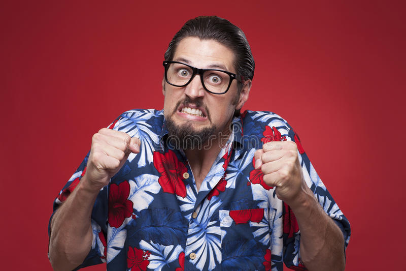 Portrait of a angry young man in Hawaiian shirt with clenched fist. stock photos