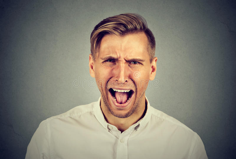Portrait angry young man screaming stock photography