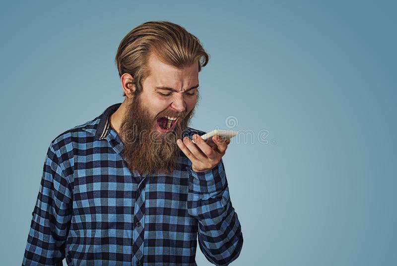 Angry young man screaming on mobile phone stock images