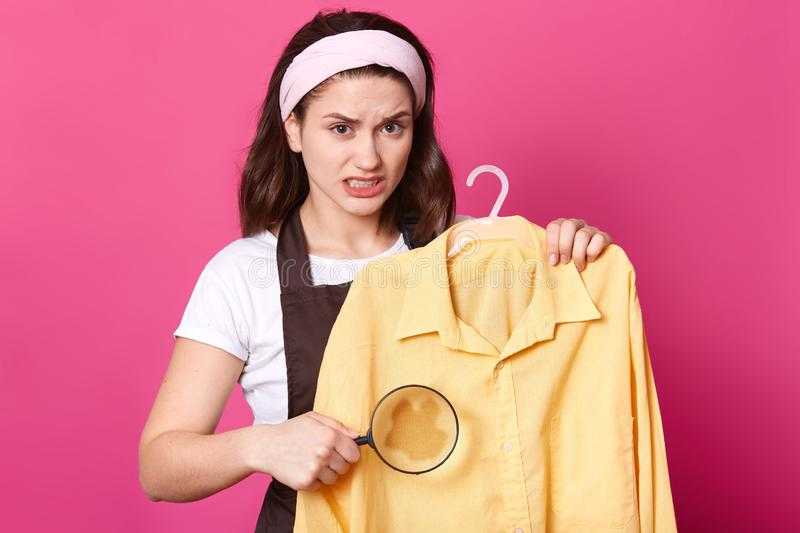 Portrait of annoyed upset woman stnading with yellow shirt on hanger, holding loupe, making stain bigger, irritated with dirt on stock image