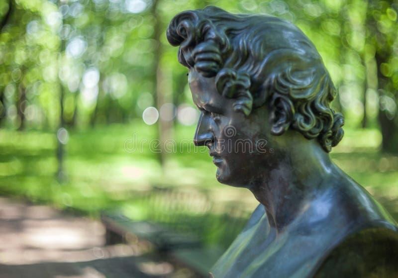 Portrait antique en bronze sculptural d'un homme dans le profil avec les cheveux bouclés sur un fond brouillé du parc photographie stock libre de droits