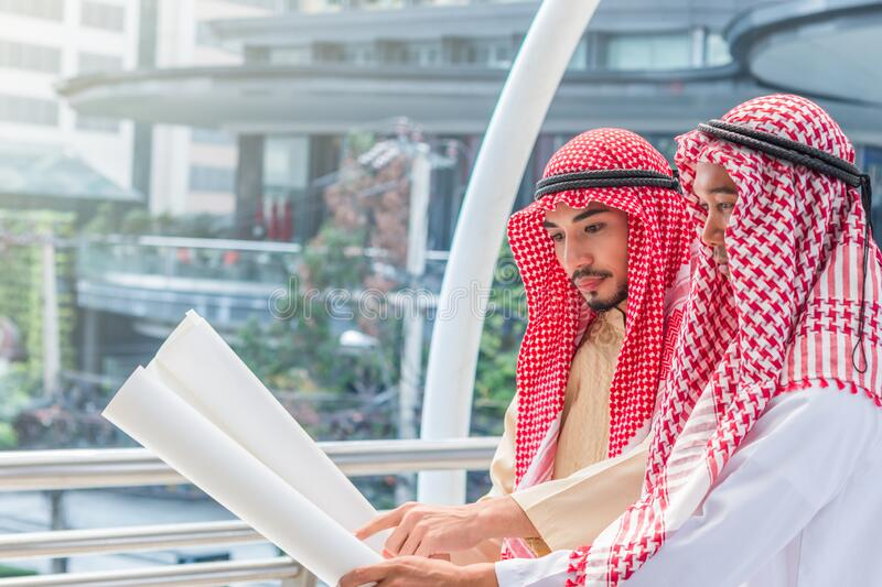 Portrait of arabian engineer talking about saudi construction job and verify the blueprint with commitment to success in downtown stock images