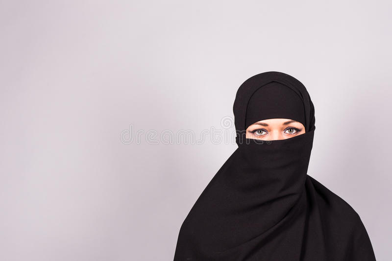Portrait of an arabic young woman with her beautiful blue eyes in traditional islamic cloth niqab. stock image