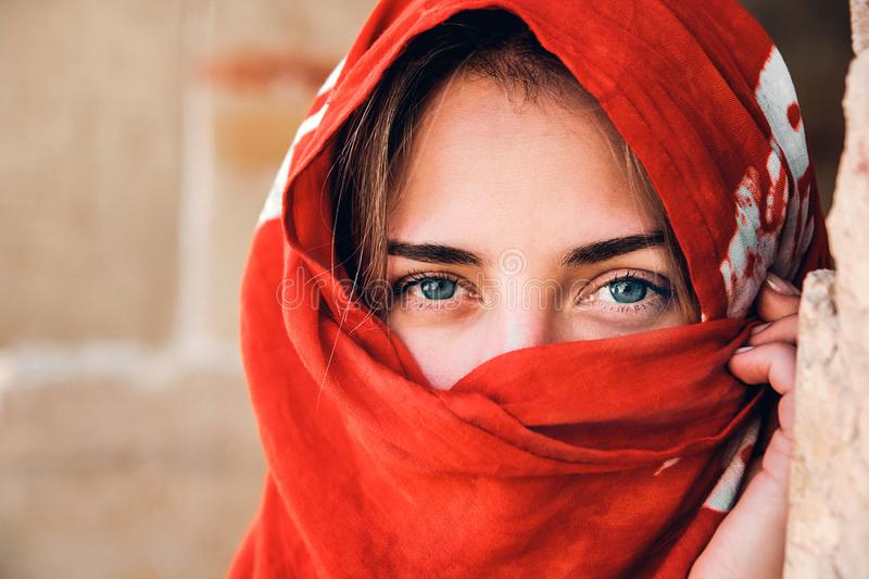 Portrait of an arabic young woman with her beautiful blue eyes in traditional islamic cloth red color. A look at the stock image