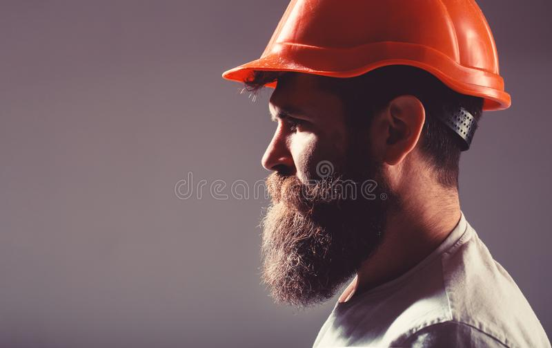 Portrait architect builder, civil engineer working. Builder in hard hat, foreman or repairman in the helmet. Bearded man stock photo