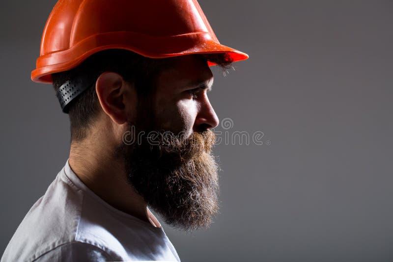 Portrait architect builder, civil engineer working. Builder in hard hat, foreman or repairman in the helmet. Bearded man royalty free stock photo