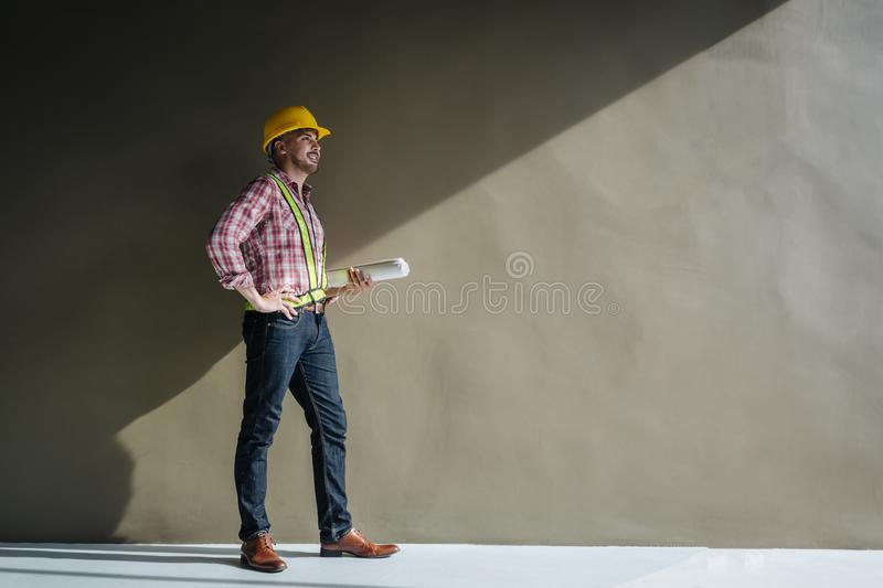 Portrait of an architect builder studying layout plan of the rooms, serious civil engineer working with documents on construction royalty free stock image