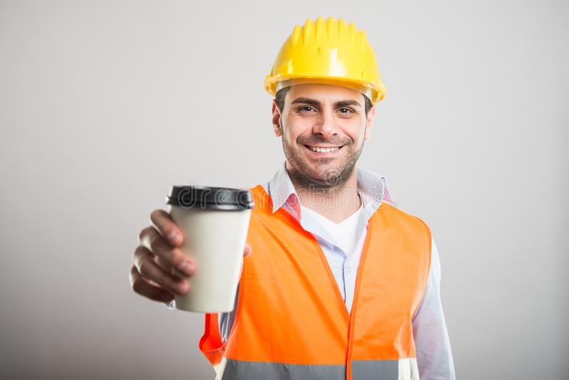 Portrait of architect offering takeaway coffee cup. And smiling on gray background royalty free stock photo