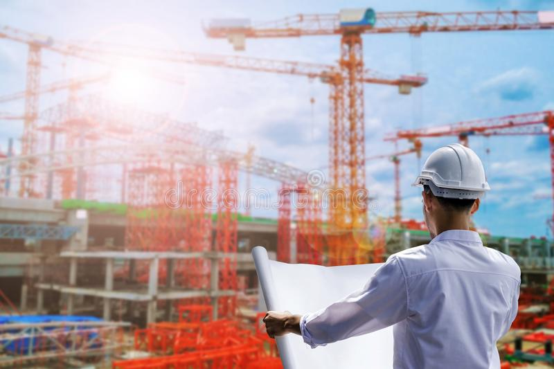 Portrait of architect at work with helmet in construction site reads the plan. Portrait of architect at work with helmet in a construction site reads the plan royalty free stock photo