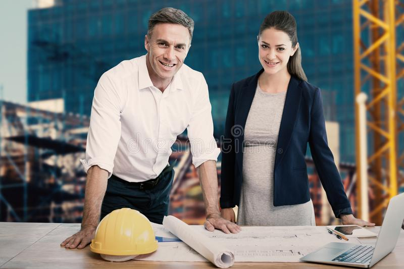 Composite image of portrait of architects standing at table royalty free stock image