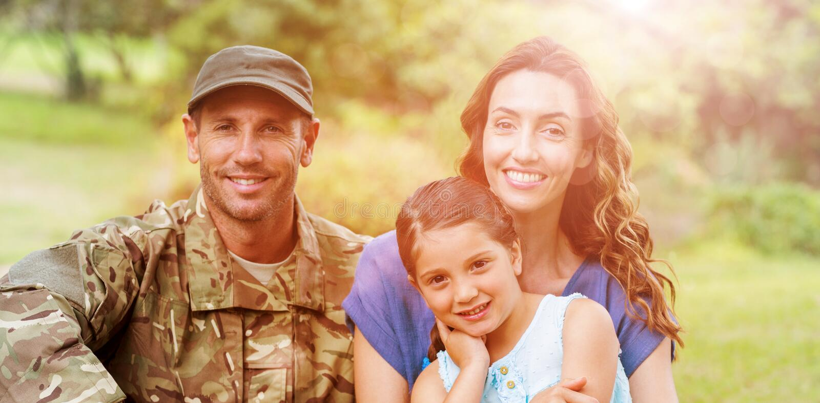 Portrait of army man with family. Portrait of smiling army men with family while sitting in park royalty free stock photo