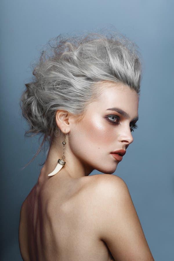 Portrait arrière d'une jeune femme avec les épaules nues, ayant des cheveux dénommant, maquillage, sur un fond bleu image stock