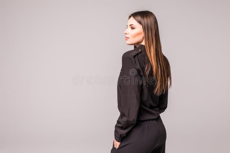 Portrait arrière de la femme avec de longs cheveux bruns de beauté - posant au studio sur le gris image stock