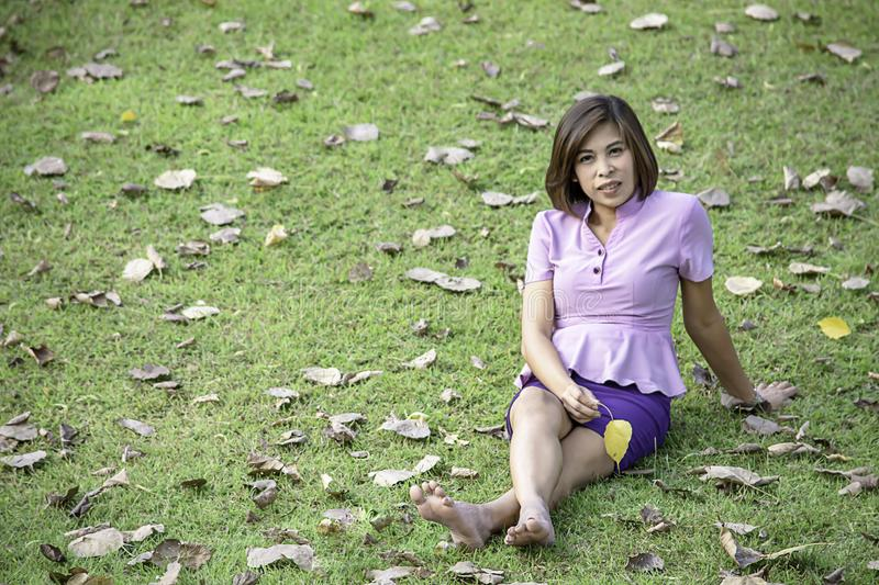 Portrait Asean woman sitting on the lawn in a park stock photos
