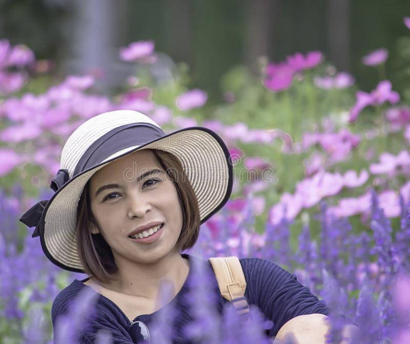 Portrait of Asean woman wearing a hat in the flower garden royalty free stock image