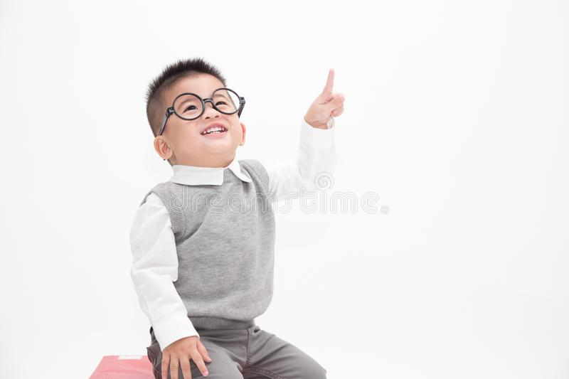 Portrait of Asian baby boy with finger pointed up. Cute little boy wearing white shirt, grey vest and glasses isolated on white background. Creative ideas and royalty free stock images