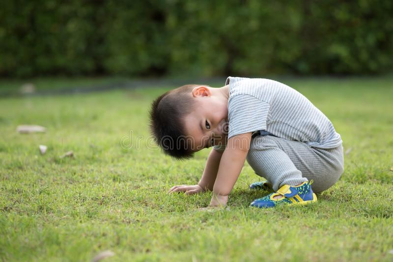 Portrait of asian baby boy sitting in park stock photography