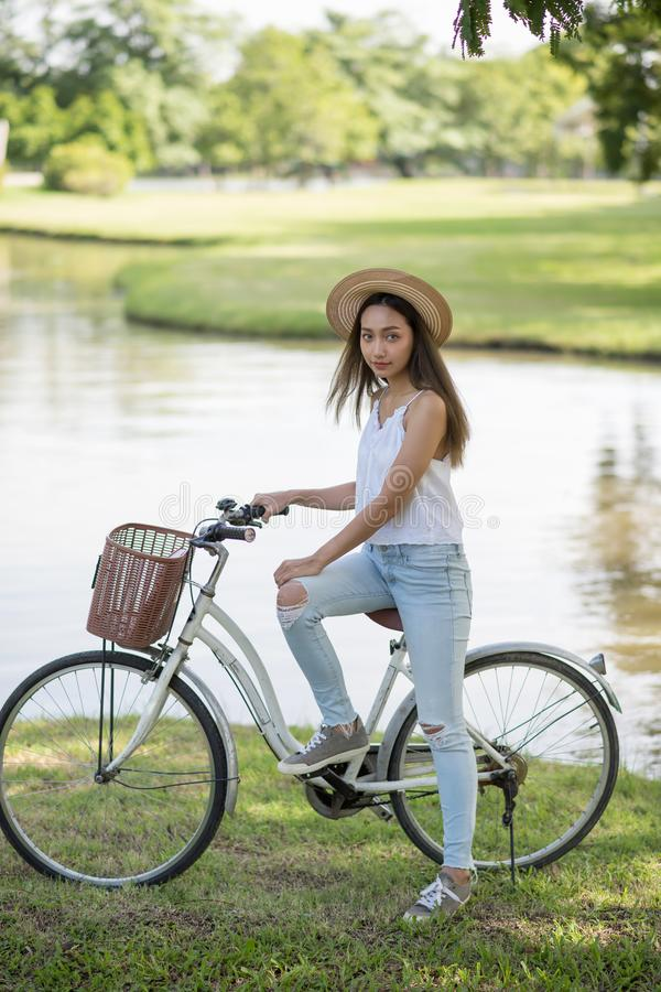 Brunette girl with bicycle in park stock photography