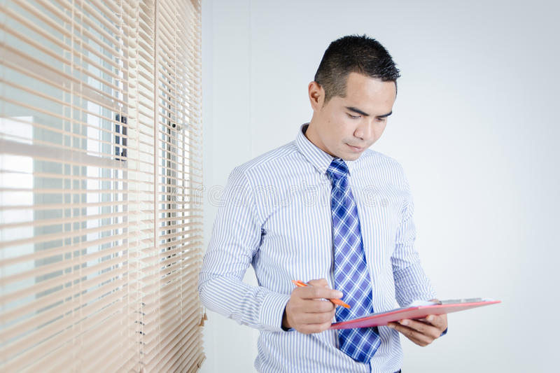 Portrait of asian business man holding clipboard and pen. In hand royalty free stock photography