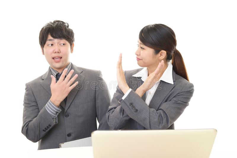 Business woman demonstrating prohibiting gesture. Portrait of Asian business people in their office stock photography