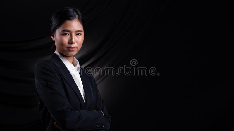 Asian Business Woman Stand in dark Formal Suit. Portrait Asian Business Woman dark blue Formal proper Suit, studio lighting black drape fabric background royalty free stock photography