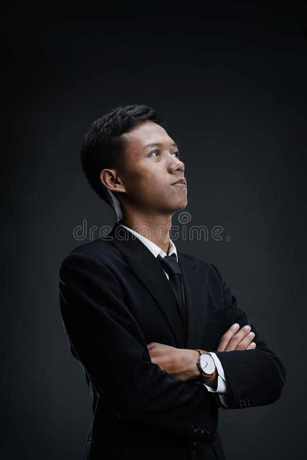 Portrait of Asian Businessman with arms crossed looking up. Dark Background royalty free stock photos