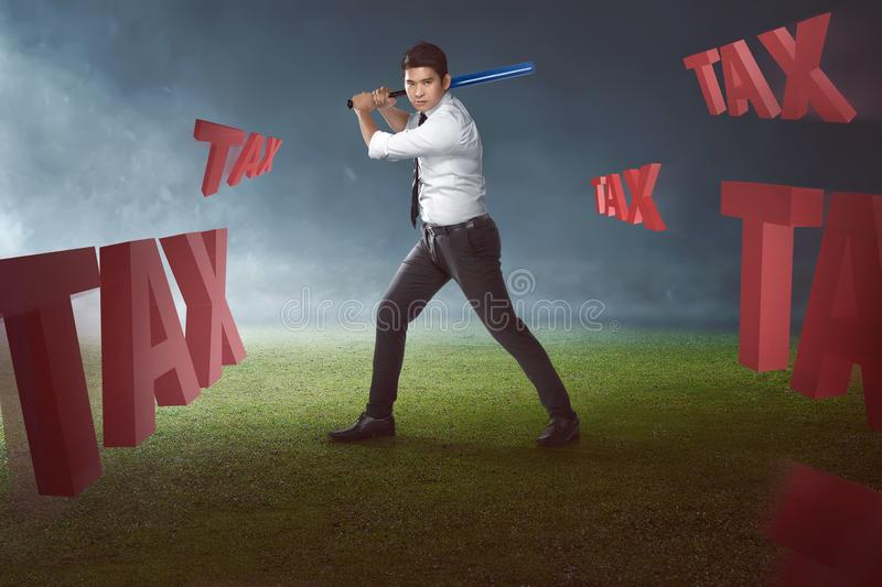 Portrait of asian businessman with baseball bat ready to hit tax stock photo