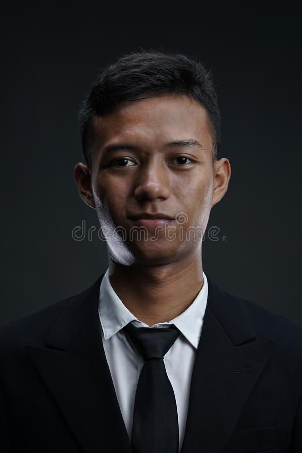 Portrait of Asian Businessman Looking Camera with Dark Background stock photo