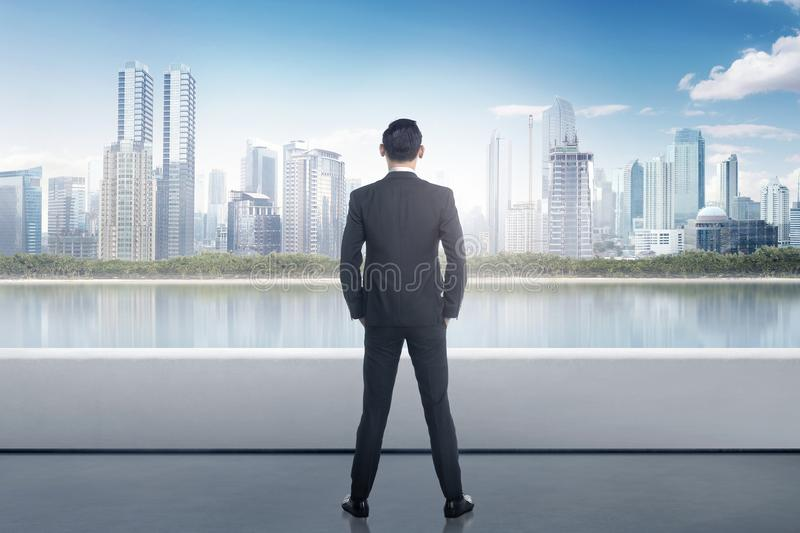 Portrait of asian businessman looking at urban scene. From building rooftop royalty free stock images