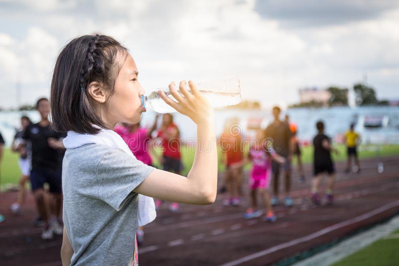 Portrait of asian child girl holding a bottle of water,drink water from a plastic bottle under the sunlight,female athlete having stock photography