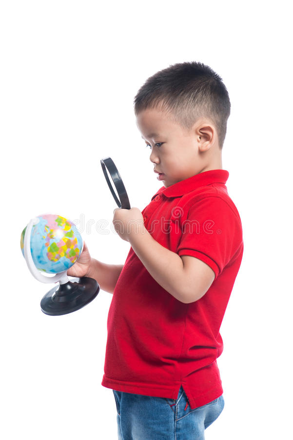 Portrait asian child holding earth globe map in his hand, looking through magnifying loupe stock images
