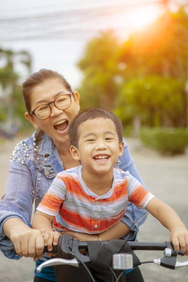 Portrait of asian children riding bicycle with mother smiling face happiness emotion royalty free stock image