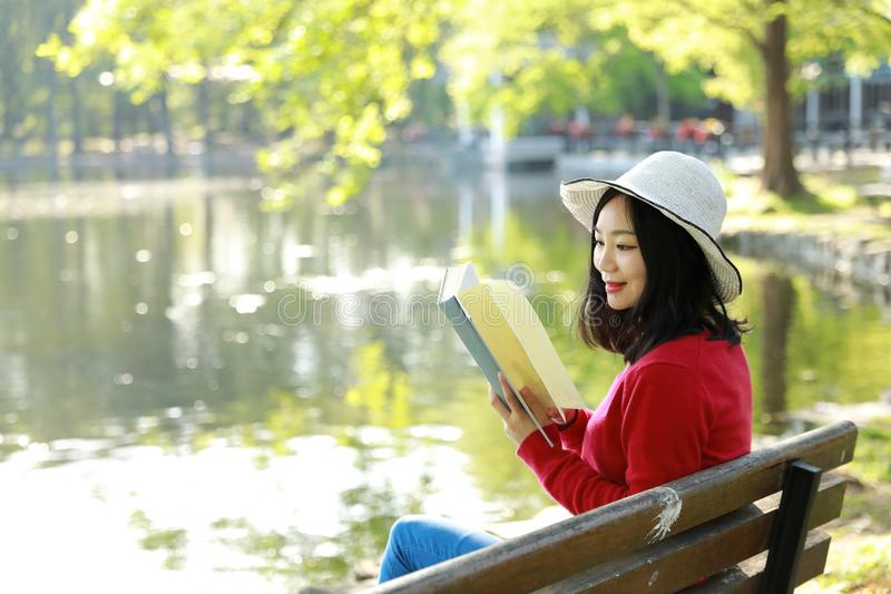 Portrait of a Asian Chinese free woman reading book in spring autumn park in forest sit on bench by a lake. Portrait of a Asian Chinese free woman reading book royalty free stock photography