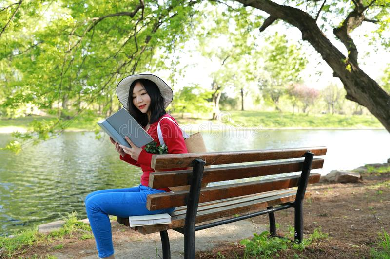 Portrait of a Asian Chinese free woman reading book in spring autumn park in forest sit on bench by a lake. Portrait of a Asian Chinese free woman reading book royalty free stock images