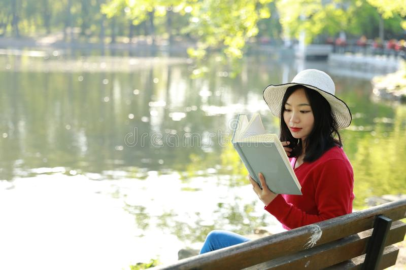 Portrait of a Asian Chinese free woman reading book in spring autumn park in forest sit on bench by a lake. Portrait of a Asian Chinese free woman reading book royalty free stock photos