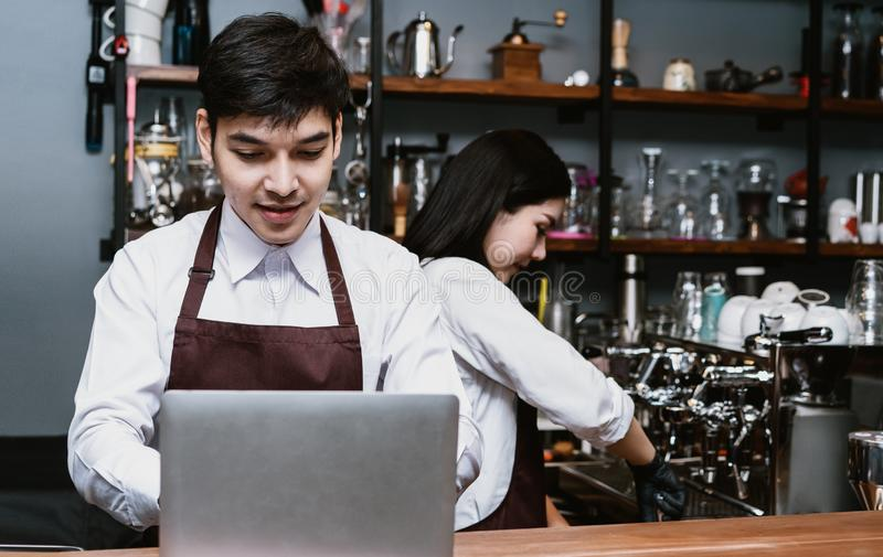 Portrait of Asian couple small business owner using laptop at counter bar in cafe, Service mind and Startup Owner small business royalty free stock photography