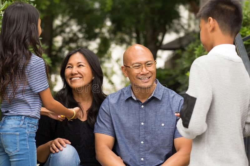 Portrait of an Asian family laughing and talking outside. royalty free stock photography