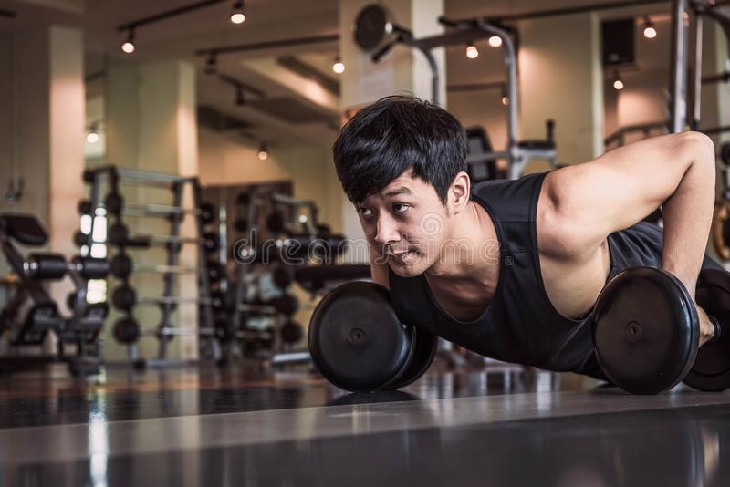 Portrait of Asian fitness man doing pushing up exercise with dumbbell in gym. People lifestyle and Sport concept. Sportsman royalty free stock photo
