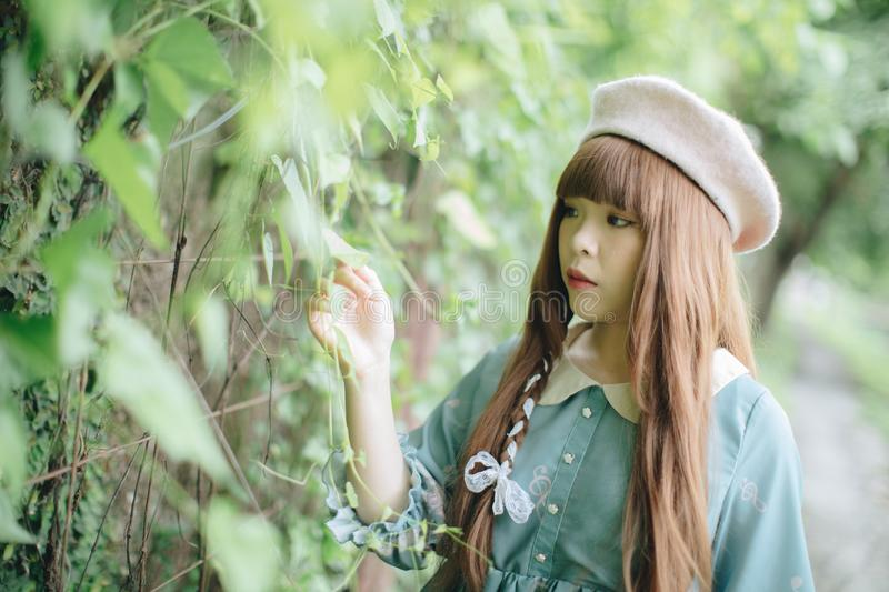 Portrait of asian girl in lolita fashion dress in garden. Background royalty free stock images