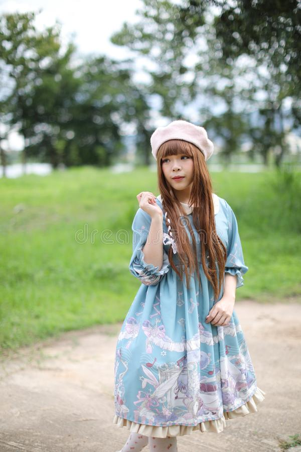 Portrait of asian girl in lolita fashion dress in garden royalty free stock photo