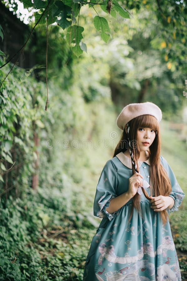 Portrait of asian girl in lolita fashion dress in garden royalty free stock photography
