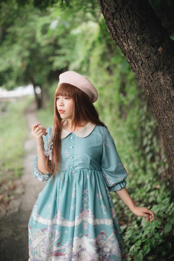 Portrait of asian girl in lolita fashion dress in garden stock photo