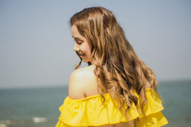 Portrait Asian girl long hair, bikini two-tone white and yellow, standing post happy posture by the sea, in Thailand South Asia, royalty free stock photography