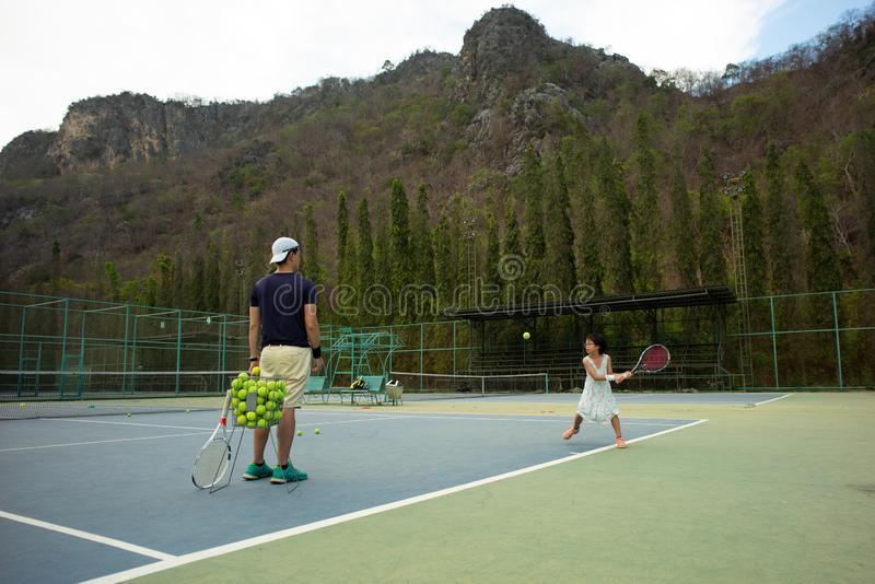 Portrait Asian girl plays tennis with her father and coach at outdoor court with stone mountain and forest background stock photos