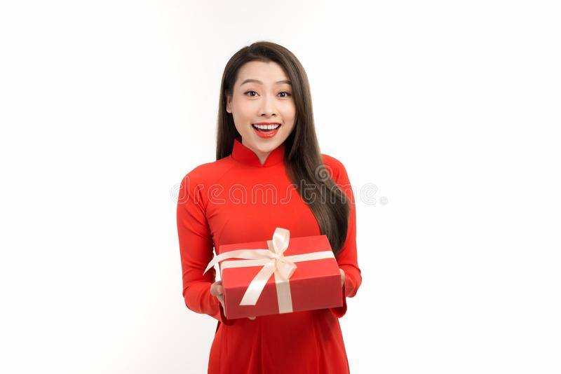Portrait of an Asian girl in a traditional Vietnamese dress, ao dai, a good smile, holding gift box royalty free stock image